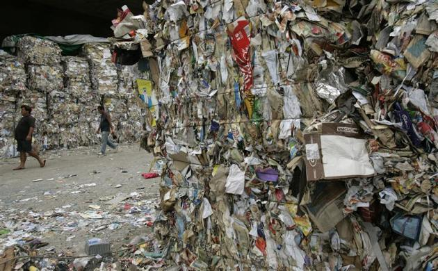 People walk near piles of waste paper products stored at a collection site before being shipped to mainland China for recycling, in Hong Kong on Earth Day April 22, 2009.