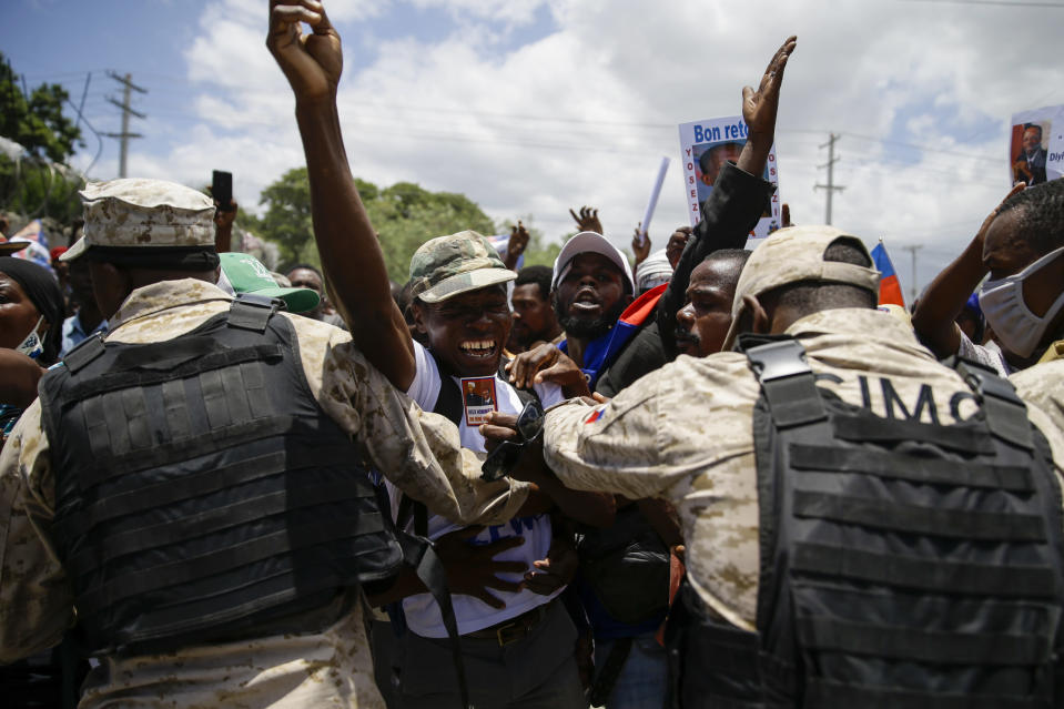 Supporters of former Haitian President Jean-Bertrand Aristide celebrate his arrival from Cuba, where he underwent medical treatment, in Port-au-Prince, Haiti, Friday, July 16, 2021. Aristide's return adds a potentially volatile element to an already tense situation in a country facing a power vacuum following the July 7 assassination of President Jovenel Moïse. (AP Photo/Joseph Odelyn)