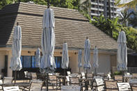 Umbrellas remain closed at an outdoor restaurant on a popular resort in Waikiki, Thursday, Oct. 15, 2020, in Honolulu. A new pre-travel testing program will allow visitors who test negative for COVID-19 to come to Hawaii and avoid two weeks of mandatory quarantine goes into effect Thursday. The pandemic has caused a devastating downturn on Hawaii's tourism-based economy and many are hoping the testing will help the economy rebound. (AP Photo/Marco Garcia)