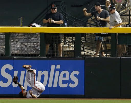 San Francisco Giants fans cheer after Giants' Juan Perez makes a leaping catch on a fly ball hit by Arizona Diamondbacks' Paul Goldschmidt during the first inning in a baseball game on Sunday, June 9, 2013, in Phoenix. (AP Photo/Ross D. Franklin)
