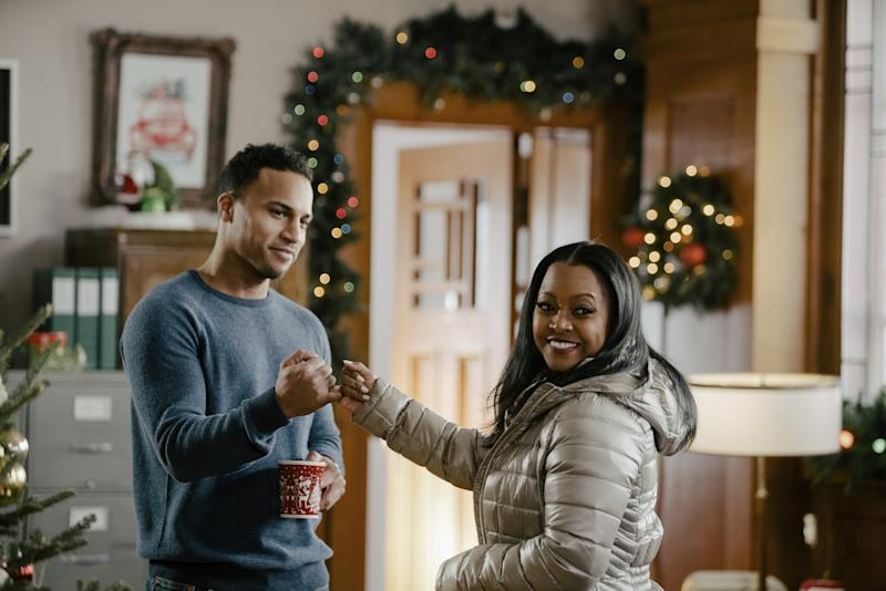 Man in blue sweater looking at woman in a silver puffy winter coat with christmas decorations in the background