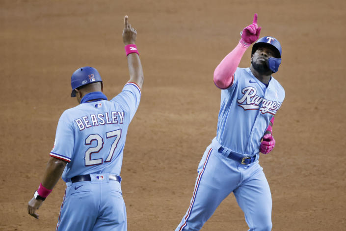 Texas Rangers center fielder Adolis Garcia (53) celebrates his three-home run against the Seattle Mariners with third base coach Tony Beasley (27) during the fifth inning of a baseball game Sunday, May 9, 2021, in Arlington, Texas. (AP Photo/Michael Ainsworth)