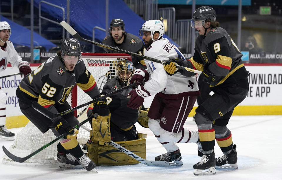 Colorado Avalanche center Pierre-Edouard Bellemare, third from left, battles for control of a loose puck with, from left, Vegas Golden Knights defenseman Dylan Coghlan, goaltender Marc-Andre Fleury, and center Cody Glass in the third period of an NHL hockey game Monday, Feb. 22, 2021, in Denver. (AP Photo/David Zalubowski)
