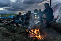 People keep warm around a bonfire at a makeshift camp for migrants and refugees near the village of Idomeni not far from the Greek-Macedonian border in April 2016 (AFP Photo/Joe Klamar)