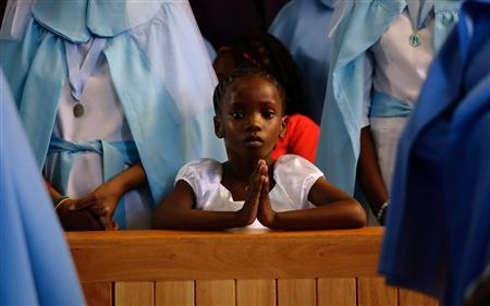 A girl prays during a service for former South African President Nelson Mandela, in the Regina Mundi Church in Soweto December 8, 2013. South African anti-apartheid hero Mandela died aged 95 at his Johannesburg home on December 5 after a prolonged lung infection. REUTERS/Kevin Coombs