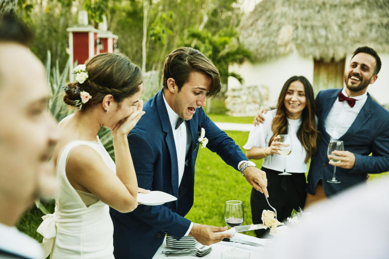 Laughing bride and groom cutting cake for guests during outdoor wedding reception