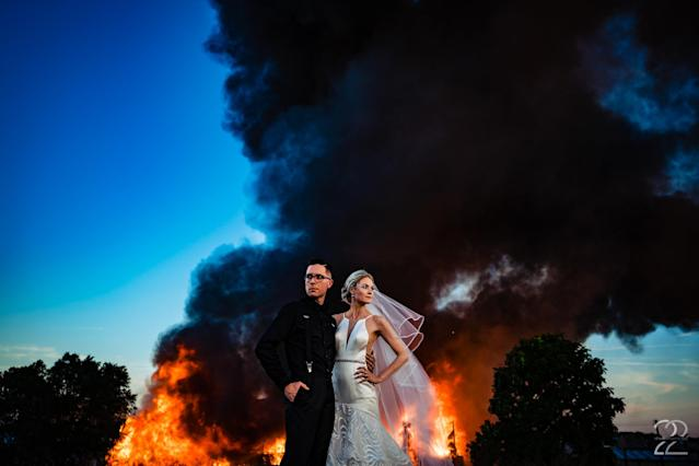 Dillon and Corrie Jameson pose against an abandoned building going up in flames. (Photo: Studio 22 Photography, Destination Wedding and Engagement Photographer)