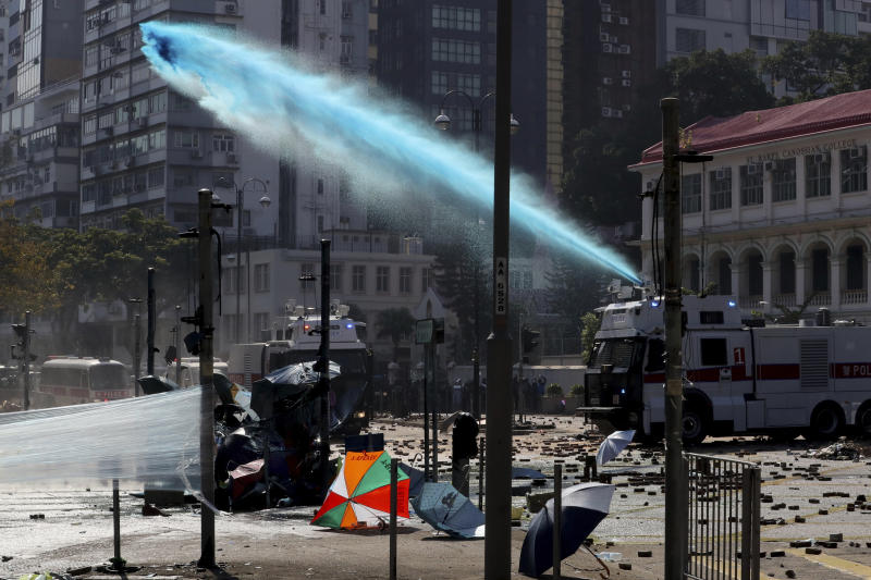 An armored police vehicle sprays blue-dyed liquid during a confrontation with protestors at the Hong Kong Polytechnic University in Hong Kong, Sunday, Nov. 17, 2019. (AP Photo/Ng Han Guan)