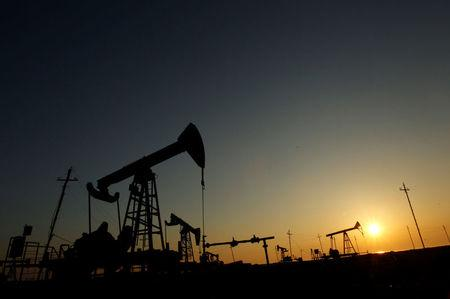FILE PHOTO: Pump jacks are silhouetted against the rising sun at an oilfield in Baku
