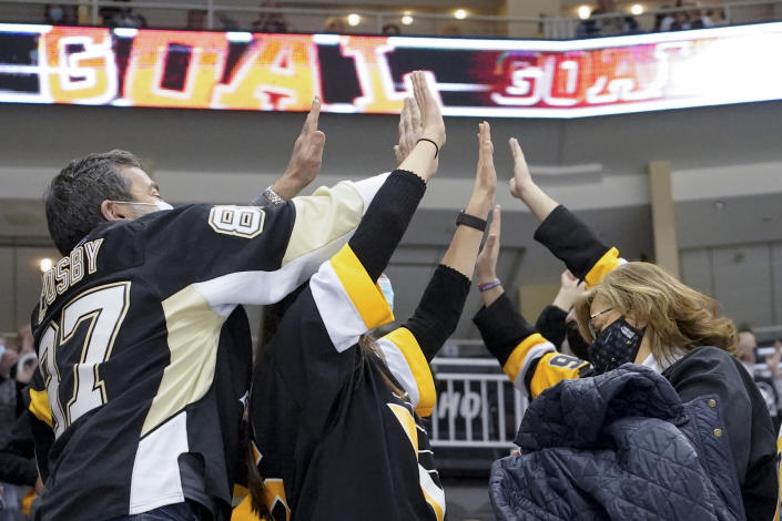 Pittsburgh Penguins fans celebrate the second goal of the period by Pittsburgh Penguins' Kasperi Kapanen (42) against the Philadelphia Flyers during the second period of an NHL hockey game, Tuesday, March 2, 2021, in Pittsburgh. It was the first game a limited number of fans were allowed to attend in Pittsburgh after some COVID 19 crowd restrictions were lifted by the state earlier this week. (AP Photo/Keith Srakocic)