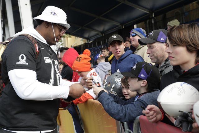AFC tackle Orlando Brown, left, of the Baltimore Ravens, signs autographs for fans during a practice for the NFL Pro Bowl football game Wednesday, Jan. 22, 2020, in Kissimmee, Fla. (AP Photo/John Raoux)