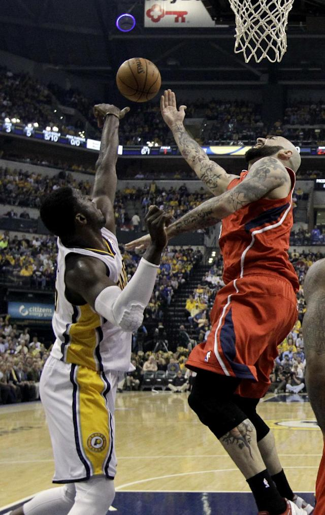 Atlanta Hawks' Pero Antic, right, has his shot blocked by Indiana Pacers' Roy Hibbert, left, during the first half in Game 5 of an opening-round NBA basketball playoff series Monday, April 28, 2014, in Indianapolis. (AP Photo/Darron Cummings)