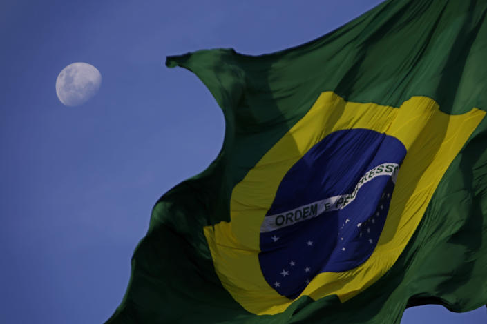 The Brazilian flag flies with the moon behind it during a protest against the government's response in combating COVID-19 and demanding the impeachment of Brazil's President Jair Bolsonaro, in Brasilia, Brazil, Sunday, Jan. 24, 2021. (AP Photo/Eraldo Peres)