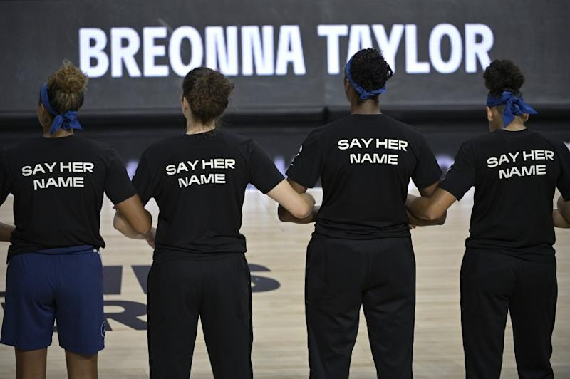 Minnesota Lynx players lock arms during a moment of silence in honor of Breonna Taylor before a WNBA basketball game against the Connecticut Sun, Sunday, July 26, 2020, in Bradenton, Fla. (AP Photo/Phelan M. Ebenhack)