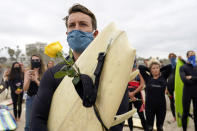 "Robert Huffman holds his surfboard and a rose as he participates in a paddle out ceremony at ""The Ink Well,"" a beach historically known as a surfing refuge for African Americans, to honor the life of George Floyd on Friday, June 5, 2020, in Santa Monica, Calif. Floyd died after he was restrained in police custody on Memorial Day in Minneapolis. (AP Photo/Ashley Landis)"