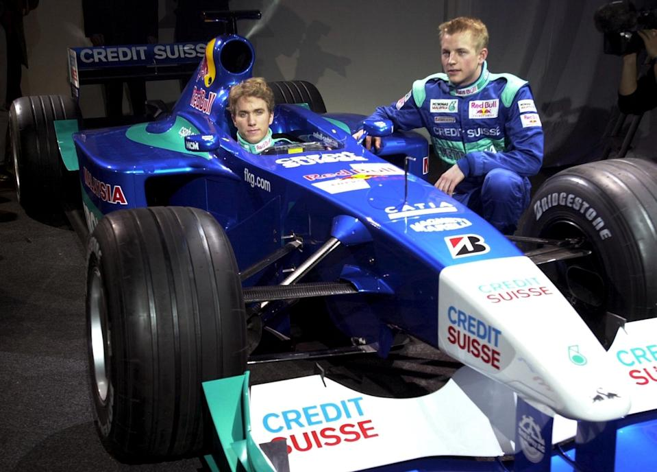 German driver Nick Heidfeld, left, sits in the cockpit of the new Red Bull-Sauber-Petronas C20 Formula One racing car, while his Finnish colleague Kimi Raikkonen, right, looks on during the car's presentation in Hinwil, Switzerland, Wednesday, Jan. 24, 2001. The Swiss racing team unveiled its blue and white racing car, which is powered by a Ferrari engine and  will have its first start during the season opener March 4 in Australia. (AP Photo/Steffen Schmidt, Keystone)