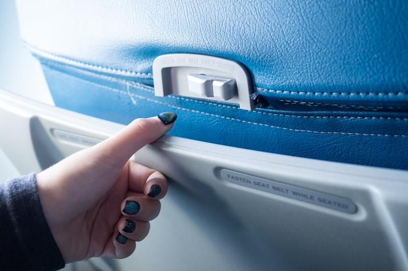 Crop image of hand open passenger food tray in airplane