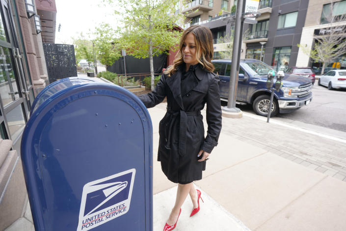 In this Tuesday, May 18, 2021, photograph, Amber McReynolds, chief executive officer of the National Vote at Home Institute, drops a letter in a mailbox outside a U.S. Post Office in the Cherry Creek shopping district in Denver. McReynolds has been confirmed by the U.S. Senate to serve on the Board of Governors of the U.S. Postal Service. (AP Photo/David Zalubowski)