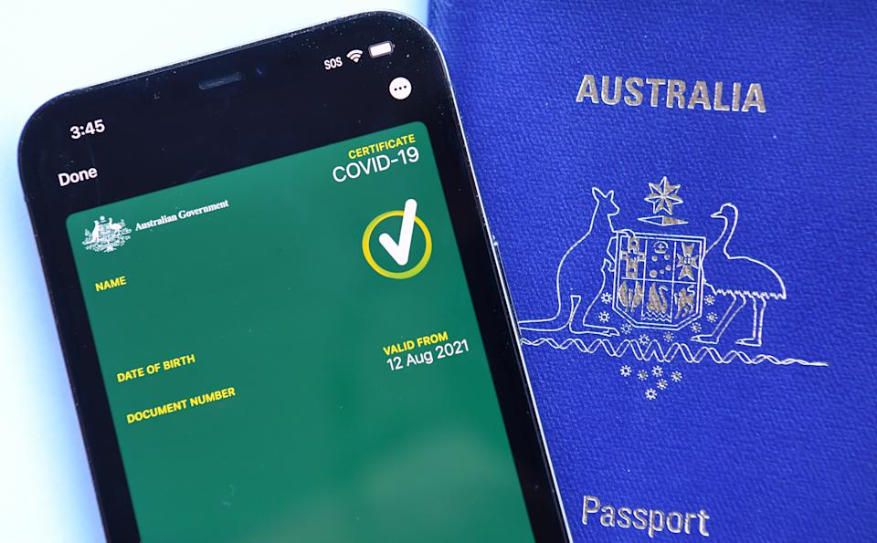 A mobile phone with an Australian Covid-19 certificate on it next to an Australian passport on August 15, 2021 in Sydney, Australia. Potential travel in Australia may require the digital vaccine confirmation in the future.