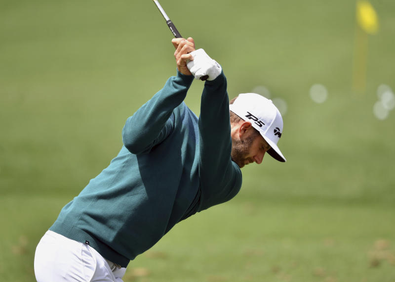 Dustin Johnson hits on the practice range before the opening round of the Masters golf tournament at the Augusta National Golf Club in Augusta, Ga., Thursday, April 6, 2017. The world's No. 1-ranked player was, however, forced to withdraw from the Masters on Thursday because of a lower back injury suffered less than 24 hours earlier in a freak fall at the home he was renting for the week. (Brant Sanderlin/Atlanta Journal-Constitution via AP)