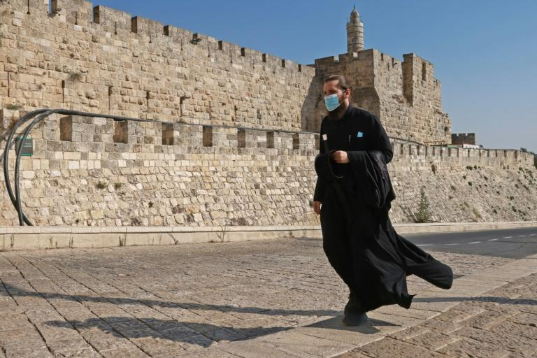 A priest, wearing a protective mask amid the Covid-19 pandemic, walks along the walls of Jerusalem's Old City on September 12, 2020