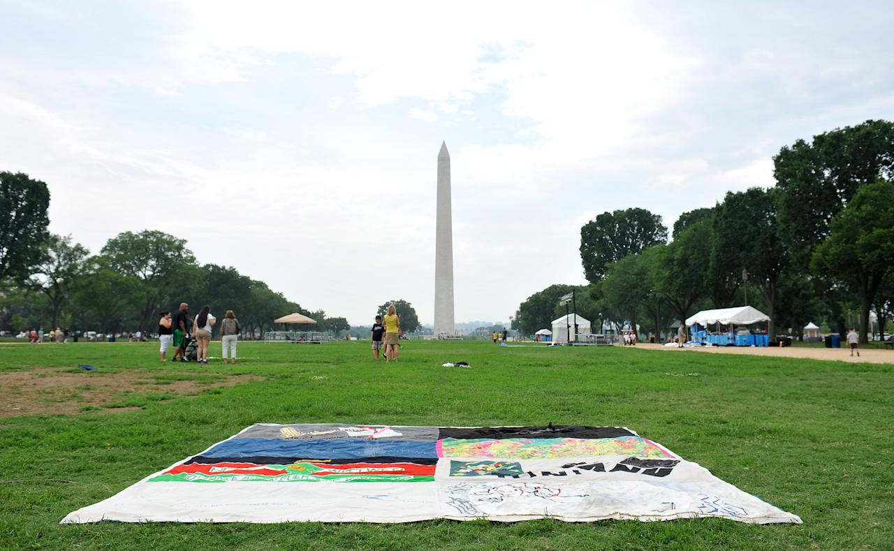 COMMERCIAL IMAGE - In this photograph taken by AP Images for AIDS Healthcare Foundation, the last panel of the AIDS quilt lays on the ground with the Washington Monument in the background during the closing of the AIDS quilt memorial, Tuesday, July 24, 2012, in Washington. The AIDS quilt memorial is being put away but not forgotten. (Larry French/AP Images for AIDS Healthcare Foundation)