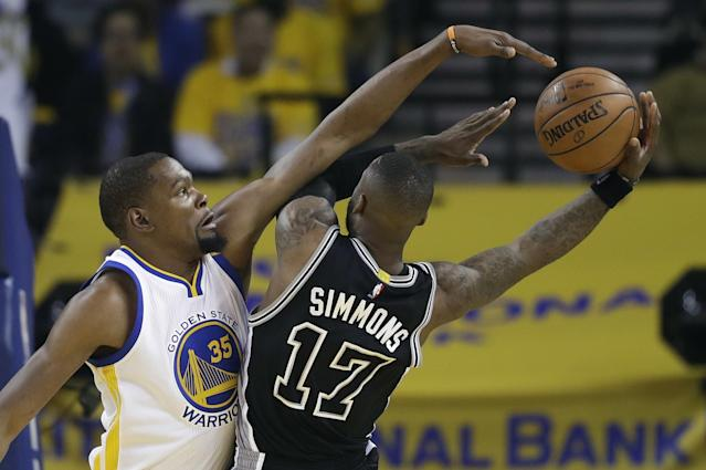 <p>San Antonio Spurs' Jonathon Simmons (17) drives to the basket as Golden State Warriors' Kevin Durant (35) defends during the first half of Game 2 of the NBA basketball Western Conference finals, Tuesday, May 16, 2017, in Oakland, Calif. (AP Photo/Marcio Jose Sanchez) </p>