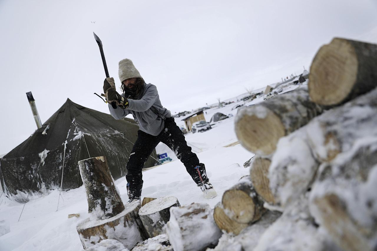 In this Tuesday, Nov. 29, 2016 photo, Blackhorse Shasta, of Oregon, chops wood on the Oceti Sakowin camp where people have gathered to protest the Dakota Access pipeline near Cannon Ball, N.D. Camp dwellers are getting ready for the hardships of a long stay. Mountains of donated food and water are being stockpiled, as is firewood, much of which has come from outside of North Dakota, the least-forested state in the nation. (AP Photo/David Goldman)