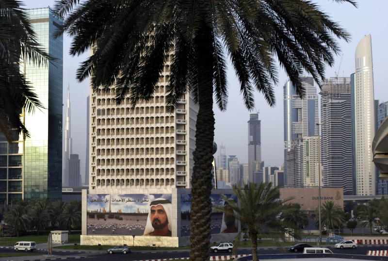 FILE - In this photo taken on Thursday, July 30, 2009, a giant billboard of Sheik Mohammed Bin Rashid Al Maktoum, UAE Prime Minister and Ruler of Dubai is seen in front of Sheikh Zayed highway towers in Dubai, United Arab Emirates. Three international banks that backed out of $10 billion debt restructuring talks with an investment company controlled by Dubai's ruler said Thursday they are now pursuing legal action against the firm, dashing hopes of a consensual deal.  (AP Photo/Kamran Jebreili, File)