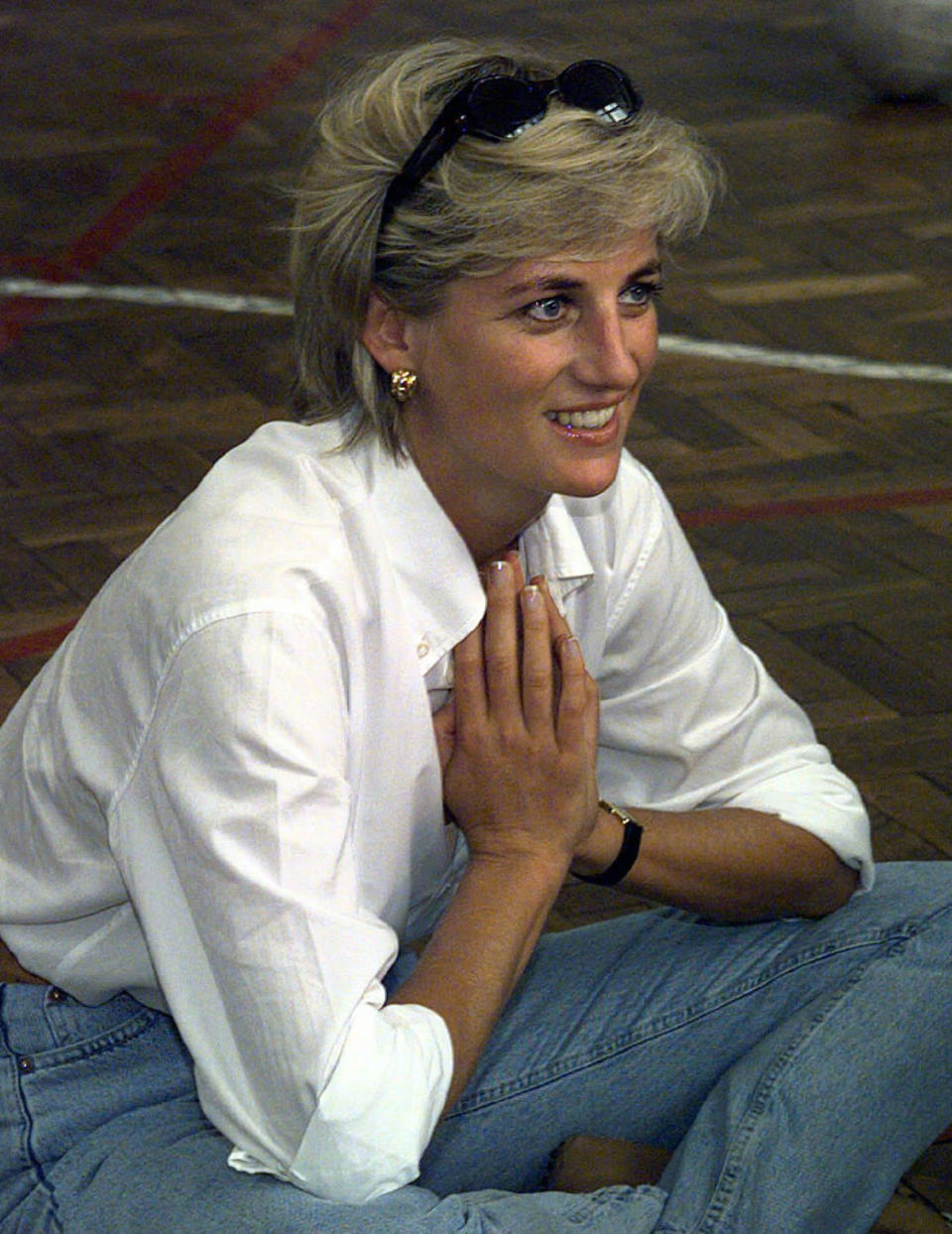 """FILE - In this Saturday, Aug. 9, 1997 file photo, Diana, Princess of Wales, sits and talks to members of a Zenica volleyball team who have suffered injuries from mines, during her visit to Zenica, Bosnia. For someone who began her life in the spotlight as """"Shy Di,"""" Princess Diana became an unlikely, revolutionary during her years in the House of Windsor. She helped modernize the monarchy by making it more personal, changing the way the royal family related to people. By interacting more intimately with the public -- kneeling to the level of children, sitting on edge of a patient's hospital bed, writing personal notes to her fans -- she set an example that has been followed by other royals as the monarchy worked to become more human and remain relevant in the 21st century. (Ian Waldie/Pool via AP, File)"""