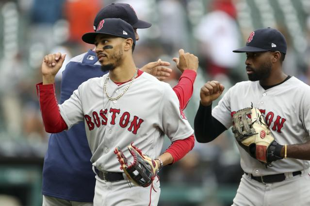 Boston Red Sox right fielder Mookie Betts, front left, and center fielder Jackie Bradley Jr., right, greet teammates after a win over the Detroit Tigers in a baseball game, Sunday, July 22, 2018, in Detroit. (AP Photo/Carlos Osorio)