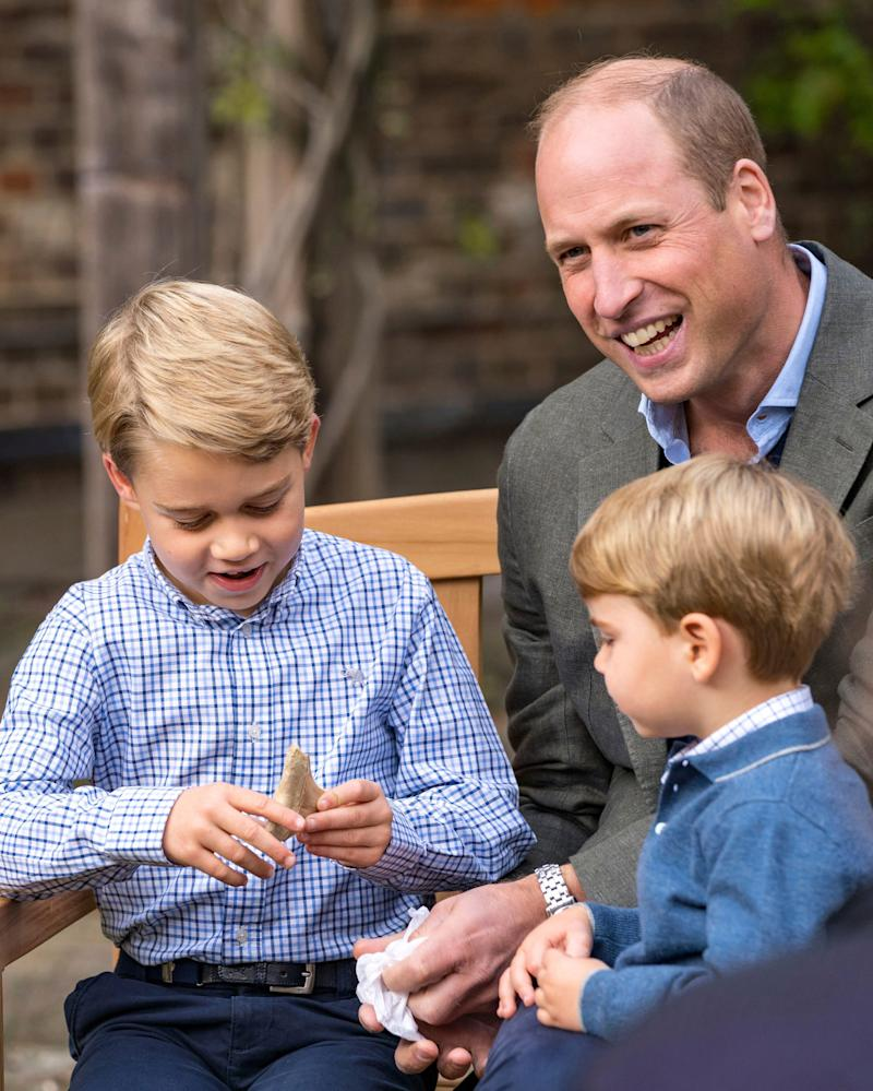 Prince George and Prince Louis with dad Prince William in the Kensington Palace gardens, examining an ancient giant shark tooth.