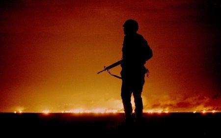 FILE PHOTO FROM GULF WAR OF U.S. SOLDIER IN FRONT OF BURNING OIL WELLS.