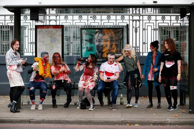 <p>People wearing costumes gather at a bus stop before participating in a zombie walk on World Zombie Day in London on Oct. 7, 2017. (Photo: Tolga Akmen/AFP/Getty Images) </p>