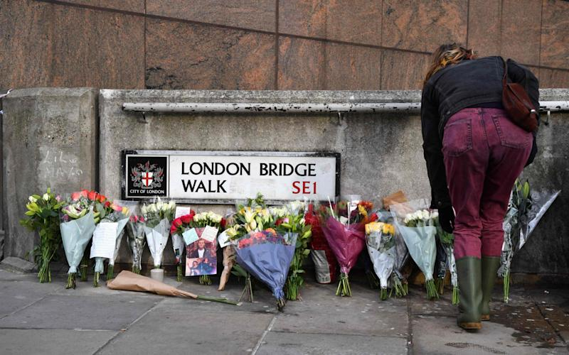 A woman places flowers with other floral tributes close to London Bridge in the City of London - AFP