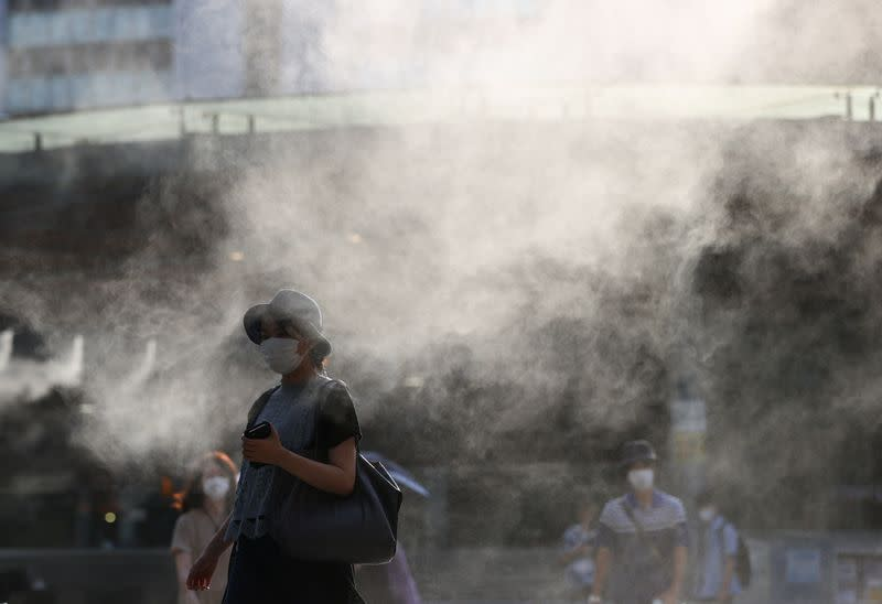 Passersby wearing protective face masks walk through a cooling mist during the Tokyo 2020 Olympic Games, amid the coronavirus disease (COVID-19) pandemic, in Tokyo
