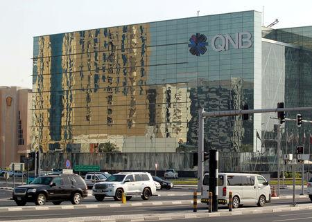 FILE PHOTO: Cars drive past the building of Qatar National Bank (QNB) in Doha