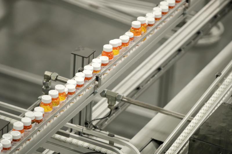 Bottles of medicine ride on a belt at the Express Scripts mail-in pharmacy warehouse, Tuesday, July 10, 2018, in Florence, N.J. (AP Photo/Julio Cortez)