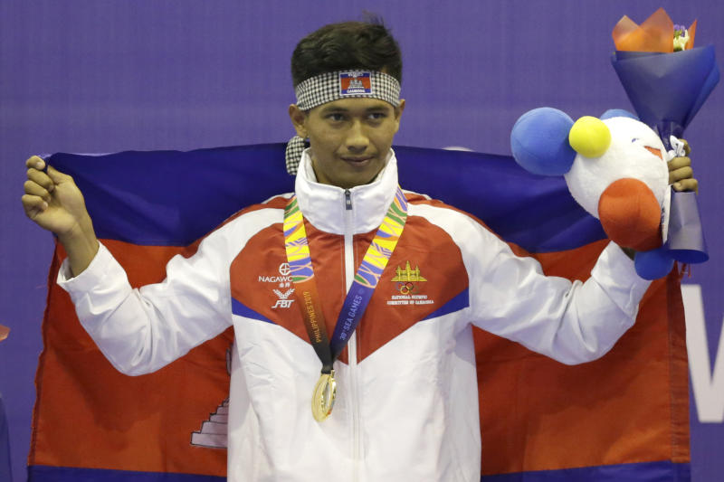 Cambodia's Mengly Yong celebrates with his medal during victory ceremony for their men's light weight +60kg-65kg padded stick competition final arnis match at the 30th Southeast Asian Games at the Clark City, Tarlac province, northern Philippines on Monday, Dec. 2, 2019. Mangly won gold. (AP Photo/Tatan Syuflana)