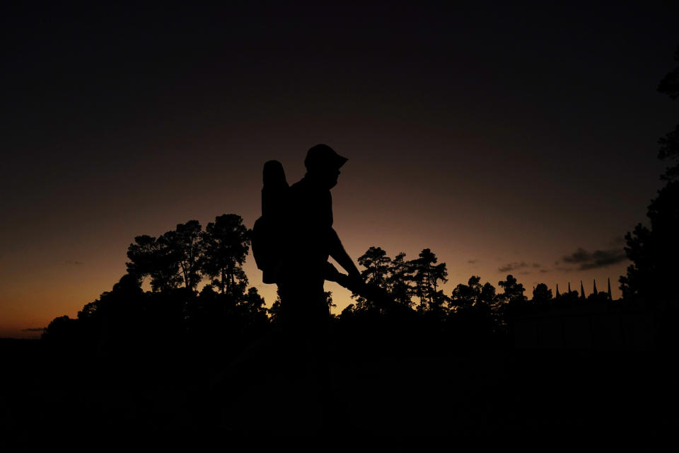A course Marshall walks off the course after sunset following the first round of the Masters golf tournament Thursday, Nov. 12, 2020, in Augusta, Ga. (AP Photo/Matt Slocum)