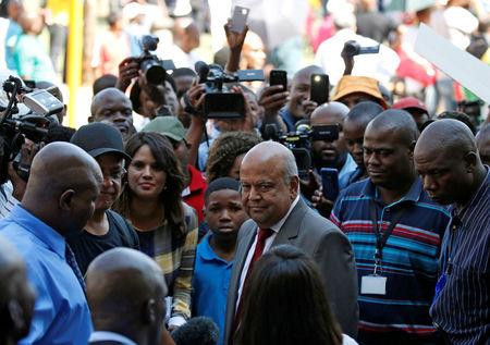 South Africa's outgoing Finance Minister Pravin Gordhan (C) looks on after speaking to supporters outside his offices in Pretoria, South Africa, March 31, 2017. REUTERS/Siphiwe Sibeko