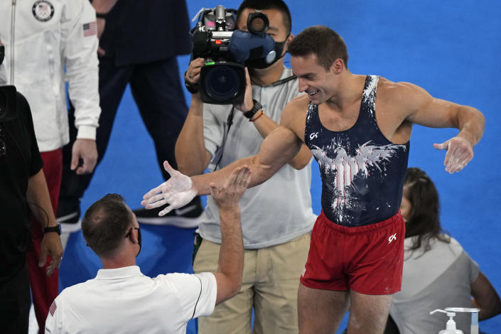 Samuel Mikulak, of the United States, gives a high five to a member of his team after performing on the vault during the artistic gymnastic men's all-around final the 2020 Summer Olympics, Wednesday, July 28, 2021, in Tokyo. (AP Photo/Gregory Bull)