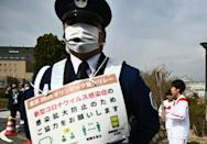 Japanese footballer Azusa Iwashimizu (R) carries the Olympic torch as a guards sign for warns about Covid-19 precautions