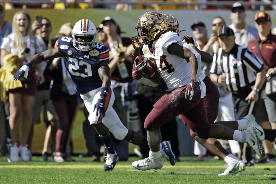 Minnesota running back Mohamed Ibrahim (24) beats Auburn defensive back Roger McCreary (23) to the endzone to score on a 16-yard touchdown run during the first half of the Outback Bowl NCAA college football game Wednesday, Jan. 1, 2020, in Tampa, Fla. (AP Photo/Chris O'Meara)