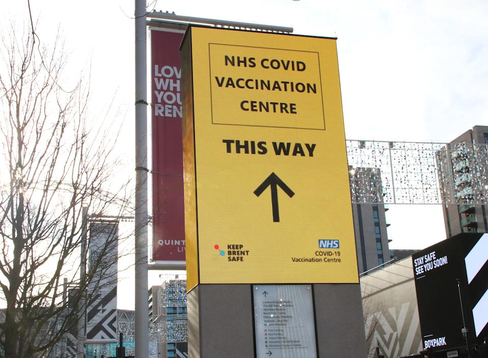 LONDON, UNITED KINGDOM - 2021/01/21: Signage directs the public to the NHS vaccination centre. A steady stream of elderly people with pre-booked appointments at the new Covid-19 Vaccination hub at theOlympic Office Centre, near London's Wembley Stadium.  It is one of 10 new large scale Vaccination centres opened this week, to join the seven already in use across the country. So far 4.9 million people across the UK have received the first dose of vaccine and the government aims for that number to rise to 15 million by 15 February. (Photo by Keith Mayhew/SOPA Images/LightRocket via Getty Images)