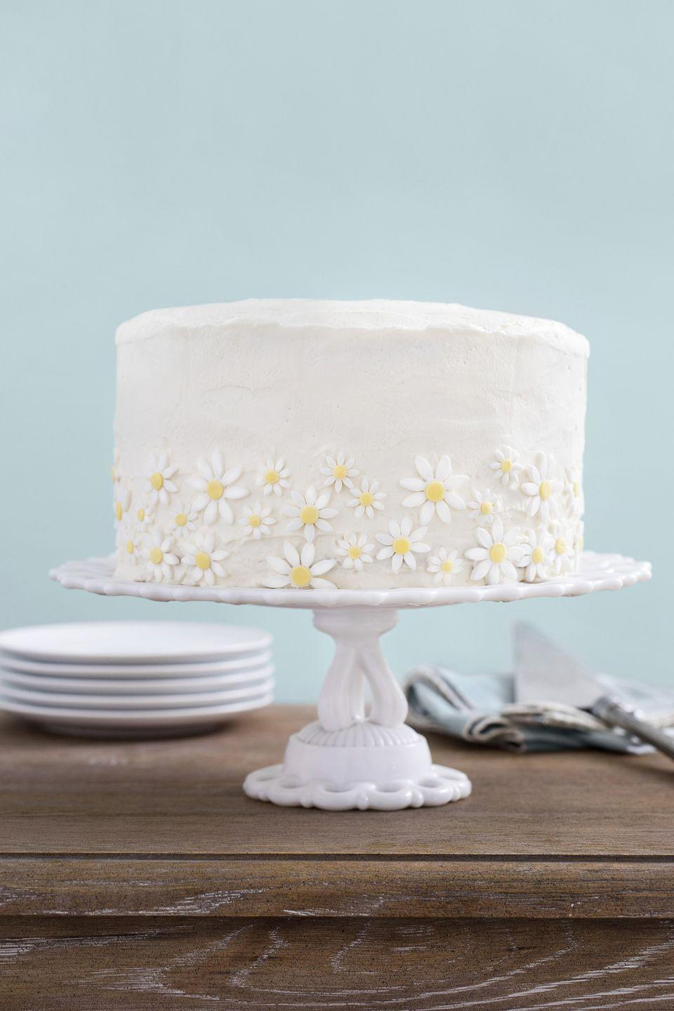 """<p>Premade fondant daisy flowers give this cake centerpiece status.</p><p><strong><a href=""""https://www.countryliving.com/food-drinks/recipes/a35037/lemon-coconut-cake-with-mascarpone-frosting/"""" rel=""""nofollow noopener"""" target=""""_blank"""" data-ylk=""""slk:Get the recipe"""" class=""""link rapid-noclick-resp"""">Get the recipe</a>.</strong></p>"""