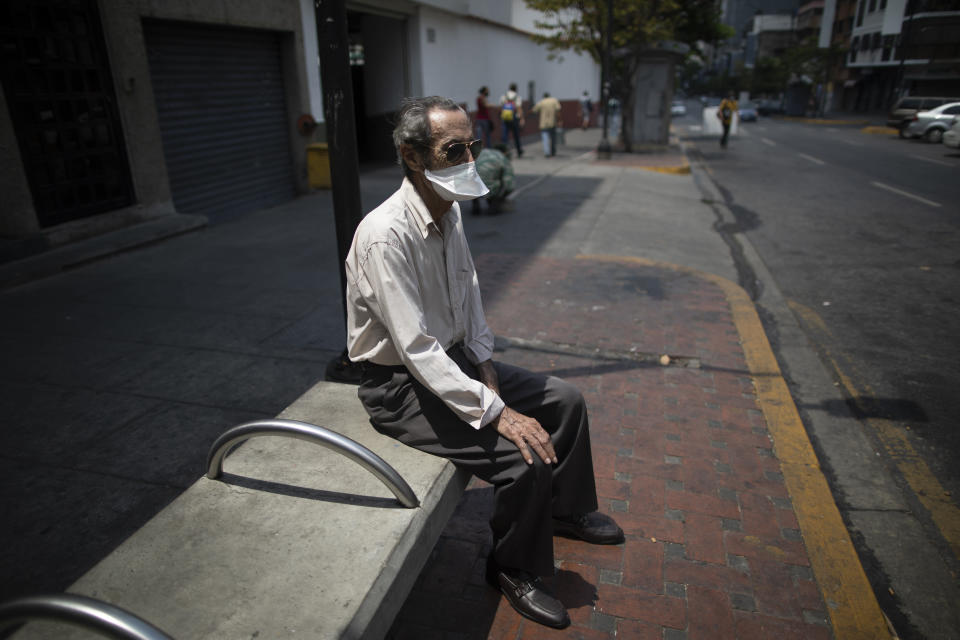 An elderly man wearing a mask to avoid the spread of the new coronavirus suns himself on a bench in Caracas, Venezuela, Sunday, May 24, 2020. (AP Photo/Ariana Cubillos)