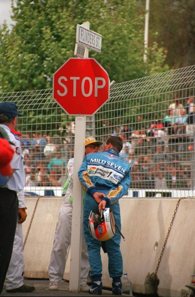 13 NOV 1994:  MICHAEL SCHUMACHER OF GERMANY STANDS AT THE TRACKSIDE AS HE IS INFORMED BY A MARSHALL THAT HE IS WORLD CHAMPION AFTER HIS CRASH WITH DAMON HILL OF GREAT BRTAIN FORCES BOTH DRIVERS TO ABANDON THE RACE. NIGEL MANSELL OF GREAT BRITAIN GOES ONTO WIN THE RACE BUT SCHUMACHER WINS THE WORLD CHAMPIONSHIP ON THE OME POINT ADVANTAGE HE HELD OVER HILL BEFORE THE START OF THE RACE. Mandatory Credit: Mike Hewitt/ALLSPORT