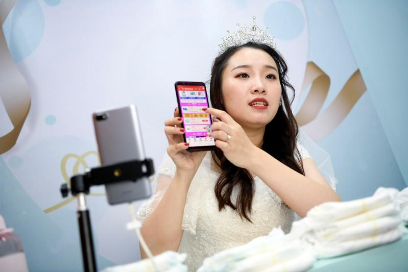 Live-streaming anchor wearing a wedding gown promotes baby diapers through a live streaming session on the eve of the 11.11 Singles' Day shopping festival, at a studio in Hangzhou