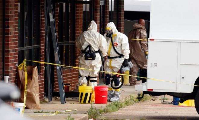 Federal authorities in hazmat suits search a small retail space on April 24 where suspect James Everett Dutschke used to operate a martial arts studio.